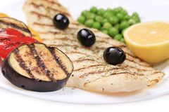 Fish fillets with vegetables on barbecue. On a white plate stock photography