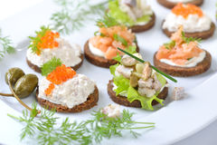 Fish finger food. Tasty fish finger food  with smoked salmon tartar, trout mousse with caviar and herring salad on pumpernickel bread Stock Images