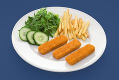 Fish fingers on blue. Three fish fingers on white plate with fries and salad - shot on a blue background Royalty Free Stock Photo