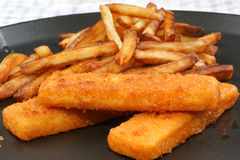 Fish fingers with chips on a pan Royalty Free Stock Photos