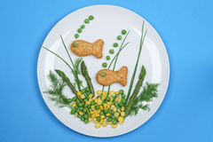 Fish fingers on a plate with vegetables Royalty Free Stock Photos
