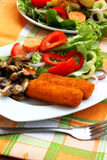 Fish fingers and salad. Plate with fish fingers, salad and mushrooms garnish stock image
