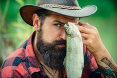 Fish and fishing concept. Fly angler man on the river. Portrait of cheerful man fishing. Angler portrait close up. royalty free stock images