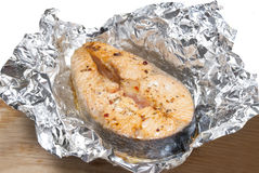 Fish in foil. Red fish with spice in foil on table Stock Photos