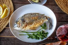 Fish food on white plate with lemon. Royalty Free Stock Photography