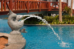 Fish Fountain under a Wooden Bridge. At Temple Bay resort, India Stock Images