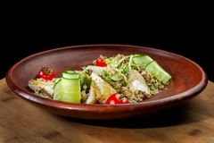 Fish with fresh green leaves salad and quinoa. The plate occupies the entire frame. Fish with fresh green leaves salad and quinoa. Clouse-up. Dish laid out on a royalty free stock photo