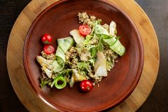Fish with fresh green leaves salad and quinoa. Clouse-up. Top view. Dish laid out on a beautiful clay plate stock image