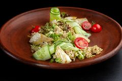 Fish with fresh green leaves salad and quinoa. Middle plan stock image