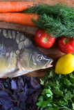 Fish with fresh vegetables and herbs. The fresh fish carp on a wooden background with vegetables and herbs Royalty Free Stock Photography