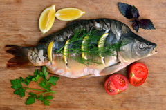 Fish with fresh vegetables and herbs. The fresh fish carp on a wooden background with vegetables and herbs Stock Photo