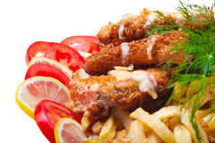 Fish fried in breadcrumbs with tomato and lemon. On a white background Stock Image
