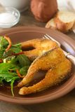 Fish fried in corn flour, served with salad, bread and wine. Royalty Free Stock Photo