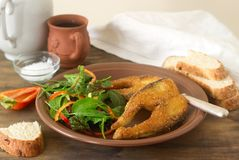 Fish fried in corn flour, served with salad, bread and wine. Stock Image