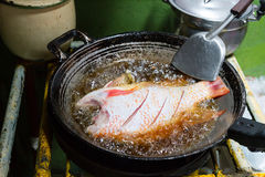 Fish fried in a wok kitchen unlit focus on the fish. Fish fried  focus on the fish Stock Photography