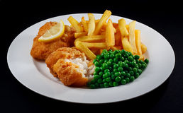 Fish, fries, peas, slice lemon. Close up of fish and chips with peas and a slice of lemon. A traditional British Seaside Dish Royalty Free Stock Photography