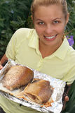 Fish fry. Young smiling woman holds fried fish stock photos