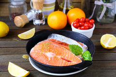 Fish in a frying pan and ingredients Stock Images