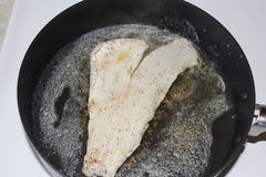 Fish Frying In Skillet. Walleye filet frying in hot oil in a skillet Royalty Free Stock Photo