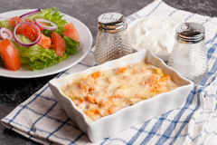 Fish gratin with cream, cheese and pumpkin. French dish julienne. Fish gratin with cream, cheese, French dish julienne, close up, horizontal Royalty Free Stock Image