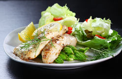 Fish on green asparagus with salad. Delicious fried fish on green asparagus with salad Stock Photography