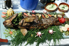 Fish grill. Fish on a barbecue with fruits and vegetables Royalty Free Stock Photography