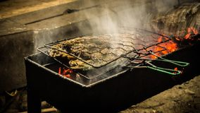 Fish grill with fire and coal and white smoke on the street food stock image