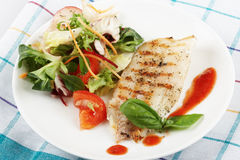 Fish grill with salad. Fish grill with tomato sauce and salad in white plate Royalty Free Stock Photography