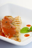Fish grill with tomato sauce. In white plate Royalty Free Stock Photography
