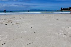 Fish Hoek Beach Sand. Close up of the sand and blue ocean at Fish Hoek Beach on a sunny day in Cape Town, South Africa Stock Photo