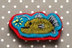 Fish. Homemade embroidered fish with lamp on a dots grey background Royalty Free Stock Photos