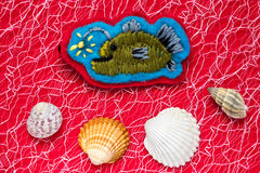 Fish. Homemade embroidered fish with lamp on a red background with seashells Royalty Free Stock Image