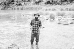 Fish on hook. Brutal man stand in river water. Man bearded fisher. Fisher masculine hobby. Fishing requires to be