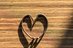 Fish hook heart. On a wooden background stock image