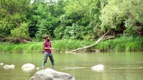 Fish on the hook. Man with fishing rods on river berth. Angler. Fly fishing is most renowned as a method for catching. Trout and salmon. Concepts of successful stock video footage