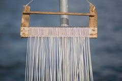 Fish hooks on wooden rack Stock Photography