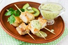 Fish kebabs on bamboo skewers with light kiwi sauce Stock Photos
