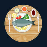 Fish with lemon and fresh herbs on a wooden desk. Royalty Free Stock Photos