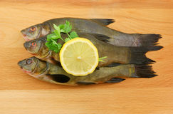 Fish with lemon and parsley on wooden background Stock Photo