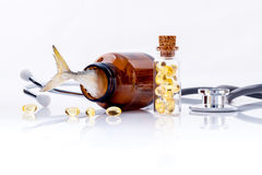Fish liver oil capsules in bottle with stethoscope. Royalty Free Stock Photo