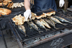 Fish mackerel and chicken tabaka grilled at bbq Royalty Free Stock Photography