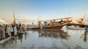 Fish market in the emirate of Ajman timelapse. United Arab Emirates. Fish market in the emirate of Ajman timelapse with people selling fish and ship in the stock image