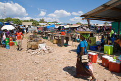 Fish market. MPULUNGU, ZAMBIA - JUNE 6, 2014: Fish market in Mpulungu. Traders sell fisch, lemons, sweets and other products. One woman carries goods on her head Royalty Free Stock Images
