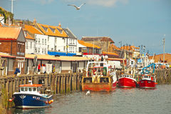 Fish Market at Whitby. Fish market in the harbor at Whitby in East Yorkshire  with a few boats tied up on a Sunday Royalty Free Stock Images