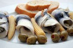 Fish meal. With rolled pieces of fish, olives, baby corn and bread stock image