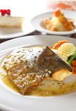 Fish meal. Fish dish with sauce on the plate. Focus on the fish, shallow field of depth Stock Photo