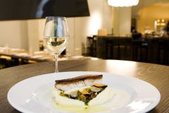 Fish meal at fancy restaurant. With glass of white wine Stock Image