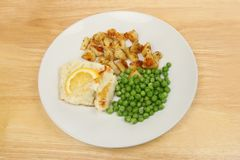 Fish meal on a tabletop. Pan fried cod with potatoes and peas on a plate on a wooden tabletop royalty free stock photography