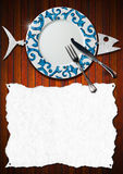 Fish Menu Design. Restaurant fish menu with metal fish, white empty paper, empty plate with silver cutlery on brown wooden background Stock Photo
