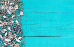 Fish netting with shells border on teal blue wood sign Stock Photography